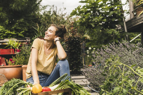 Young woman with eyes closed sitting by vegetables and plants in community garden - UUF21025