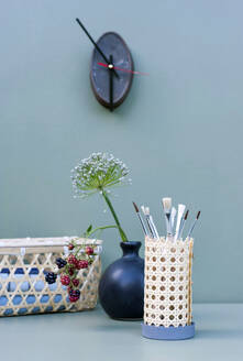 Vase with flowers and DIY rattan desk organizer with paintbrushes - GISF00637