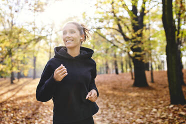 Young woman jogging in autumn forest - BSZF01684
