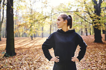 Young woman jogging in autumn forest - BSZF01687