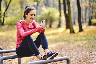 Young female jogger using smartphoneon sitting on bicycle stand in autumn forest - BSZF01693
