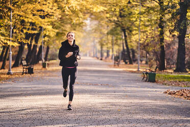 Young woman jogging in autumn forest - BSZF01696