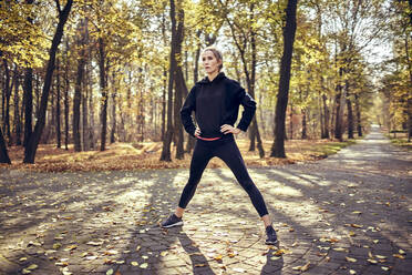 Young female jogger standing with open legs in autumn forest - BSZF01702