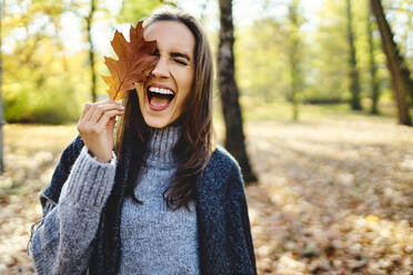 Young laughing woman holding autumn leave on her eye - BSZF01711