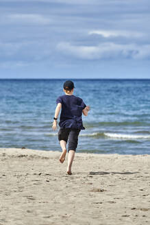 Boy running on beach during sunny day against sky - JEDF00330