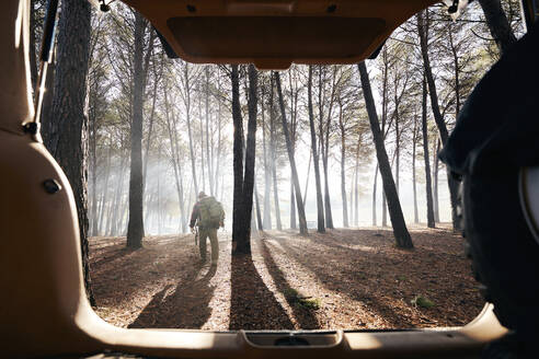 Buscrafter hiking in forest seen from car trunk - SASF00034