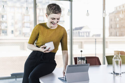 Smiling businesswoman sitting on desk in office holding coffee mug and using tablet - UUF21126