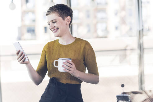 Smiling businesswoman in office holding coffee mug and mobile phone - UUF21135