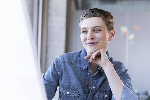 Portrait of smiling businesswoman at desk in office - UUF21162