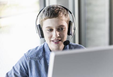 Businesswoman wearing headset at desk in office - UUF21183
