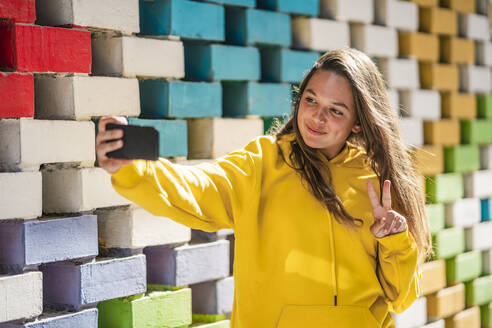 Young woman taking selfie on smart while standing by colored brick wall - DLTSF01125