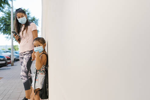 Woman with face mask using mobile phone while looking at girl leaning on white wall - EGAF00682