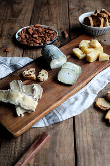 Sweet croutons with raisins and plate with almonds placed on wooden table near board with various cut cheese - ADSF14464