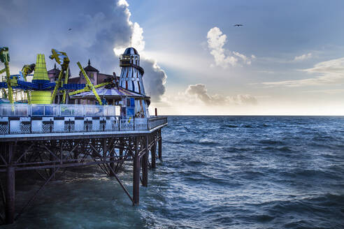Colorful attractions of amusement park on pier near waving sea against cloudy sky in evening in Brighton, England - ADSF14599
