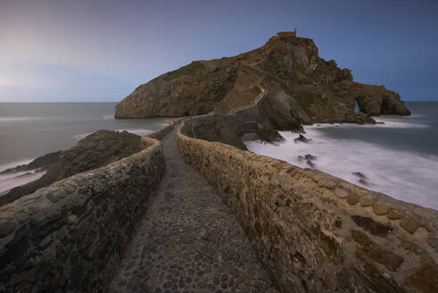 Waves beating against medieval stone bridge leading to small rocky island with San Juan de Gaztelugatxe hermitage on top at Spanish coast in sunny day with blue sky in background - ADSF14632