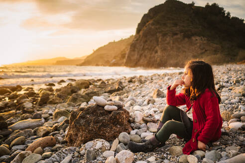Side view of pensive female kid sitting on stony beach and admiring sundown on background of calm seaside - ADSF14656