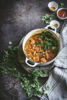 Top view of bowl of delicious vegan chickpea curry with herbs placed near fabric napkin on gray tabletop - ADSF14692