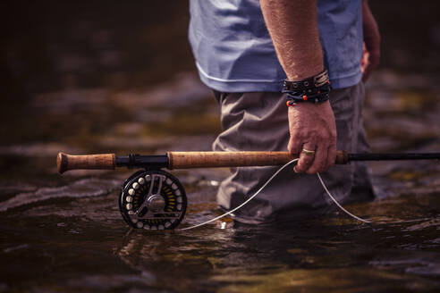 Close-up of fisherman hand holding fishing rod in hand while standing in river - DHEF00349
