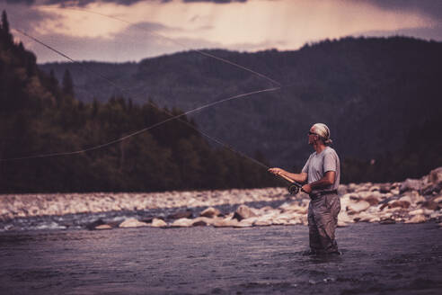 Fly fisherman casting with fishing rod while standing in river - DHEF00355