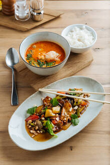 Top view of colorful vegetables in oval plate with chopsticks on wooden table with spicy seafood soup and with of boiled rice - ADSF14750
