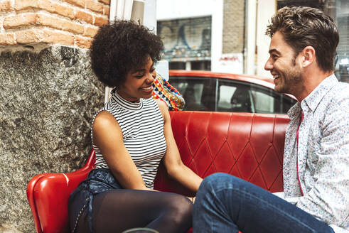 Cheerful couple talking while relaxing on sofa against window in restaurant - EHF00817