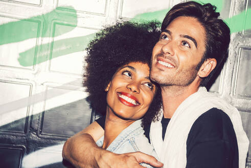 Close-up of smiling man looking up while embracing girlfriend against wall at night - EHF00891