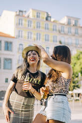 Young woman wearing hat to cheerful female friend while standing in city - DCRF00789