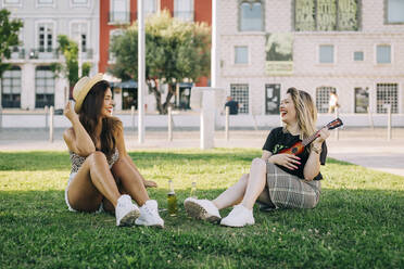 Cheerful woman playing ukulele while sitting with female friend on grassy land - DCRF00792