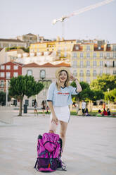 Beautiful woman wearing hat standing with backpack on footpath in city - DCRF00801