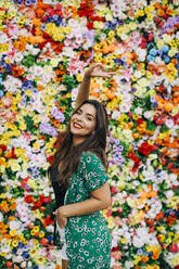 Beautiful woman showing peace sign while standing against colorful flowers - DCRF00807