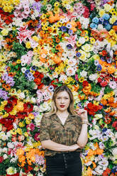 Confident beautiful woman standing against colorful flowers - DCRF00810
