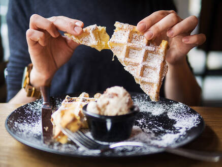 Anonymous person breaking off piece of soft waffle over plate with tasty ice cream while sitting at table in restaurant - ADSF14863