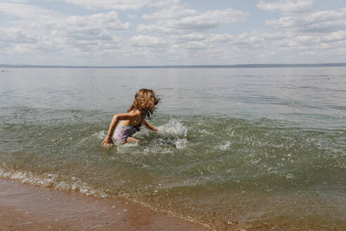 Little girl enjoying while playing in water at beach - OGF00492