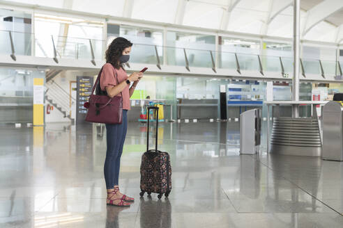 Young woman with protective face mask text messaging on smart phone while standing at airport - MTBF00662