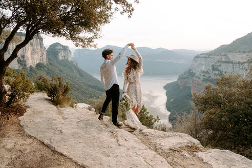 Full length of romantic young newlywed couple in elegant costumes with wedding bouquet dancing on edge of rocky cliff of Morro de Labella in Spain - ADSF14974