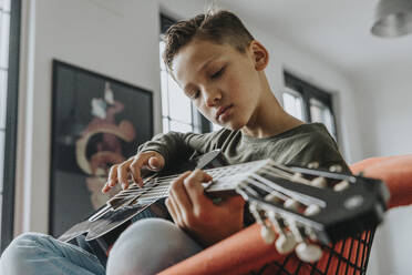 Close-up of boy playing guitar while sitting on chair at home - MFF06116