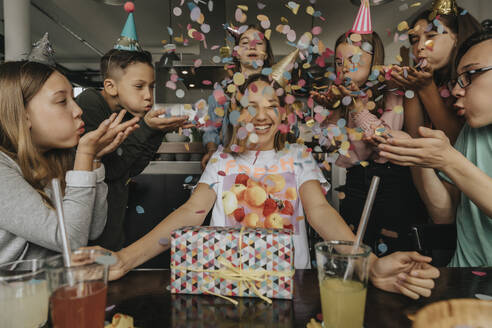 Happy friends throwing confetti on teenage girl sitting with birthday gift at dining table - MFF06125