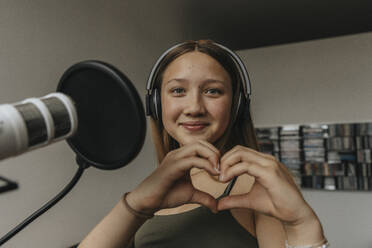 Close-up of smiling teenage girl making heart shape while singing in recording studio - MFF06173