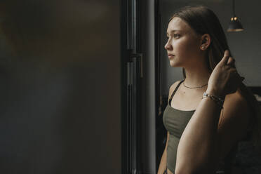 Thoughtful teenage girl looking through window while standing at home - MFF06179