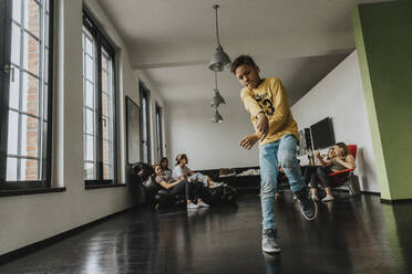 Friends looking at boy breakdancing on floor in house - MFF06182