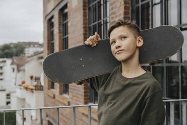 Thoughtful boy posing with skateboard while standing against building - MFF06185