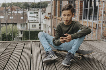 Boy using smart phone while sitting on skateboard against railing - MFF06188