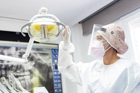 Doctor in protective workwear adjusting electric lamp in clinic - JCMF01273