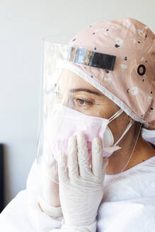 Doctor in protective suit adjusting face mask at office - JCMF01279