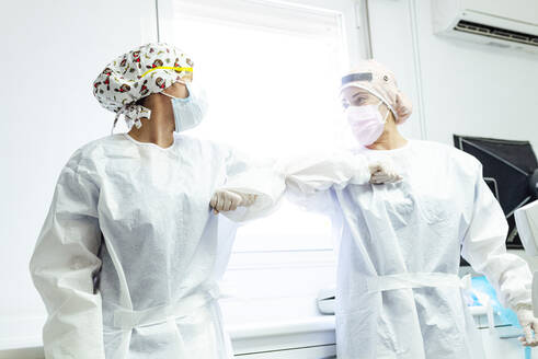 Dentist and assistant in protective workwear avoiding handshakes while standing at clinic - JCMF01282