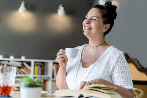 Cheerful young woman looking away while sitting with coffee and book in cafe - GIOF08788