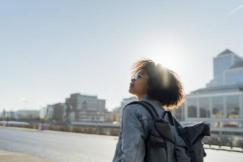Young woman with backpack standing against clear sky in city during sunny day - BOYF01443