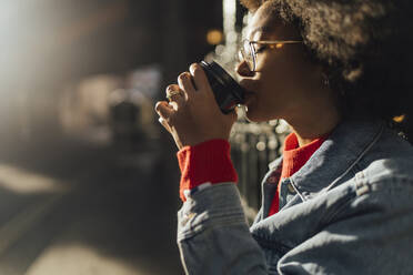 Close-up of young woman with eyes closed drinking coffee while standing outdoors - BOYF01449