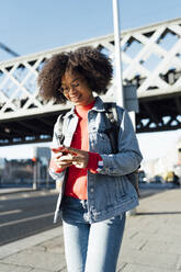 Afro young woman using smart phone while standing on sidewalk against bridge in city - BOYF01452