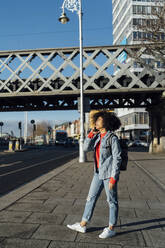 Afro woman talking over mobile phone while standing on sidewalk in city - BOYF01455